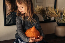 The Cute Girl Holding A Pumpkin In Her Hands Sitting On The Table.