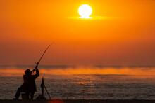Fisherman Fishing In The Sea Or Ocean Beach During Sunrise. Swinging A Rod