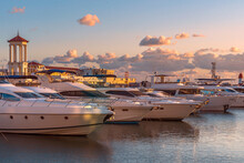 Modern Expensive Boats Are Moored At The Dock Of The Seaport And Are Illuminated By The Golden Rays Of The Setting Sun