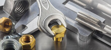 Wrench Tightens Brass Bolt In Steel Billet. Spanner, Bolt, Screw And Nuts.