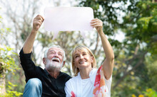 Portrait Of Senior Caucasian Couple Displaying Blank Banner Ad In The Park. Happy Elderly Couple Holding Empty White Board Plank In A Summer Park. Mature Retired Couple With Blank Banner Mock Up.