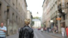 Attractive Blond Stands Looking At The Camera, Then Turns Around And Walks Away. The Guy Walks The City