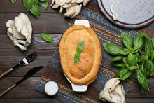 Baking Dish With Tasty Mushroom Pot Pie And Ingredients On Black Wooden Background
