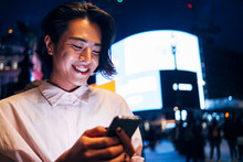 Happy Man Text Messaging Through Smart Phone In City At Night
