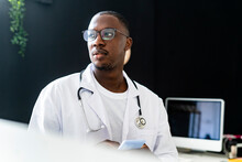 Male Doctor Wearing Stethoscope Holding Smart Phone At Medical Clinic
