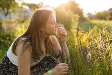 Woman Smelling Hyssop Flower In Back Yard