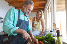 Happy Caucasian Mature Couple Cooking Together In The Modern Kitchen