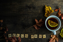 Cup Of Lemon Tea On A Table With Autumn Leaves And The Words Hello Fall