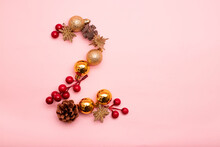Number 2 Made With Christmas Ornaments On A Pink Background