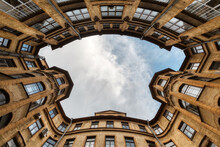 Photo Of Symmetrical Courtyard In Residential House From Historical Center Of Saint Petersburg In Russia. Blue Cloudy Sky. The Facade With Two Bay Windows Is Decorated With Sculptures Of Gargoyles.