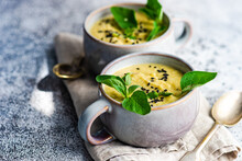 Two Cups Of Creamy Spicy Chickpea Soup With Oregano And Black Sesame Seed Garnish