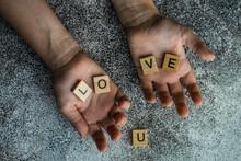 Overhead View Of Hands Holding Wooden Blocks Spelling Love U