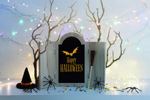 Holidays Image Of Halloween. Witch Hat, Broom, Bare Trees, Wooden Board Frame With Text Over White Wooden Table
