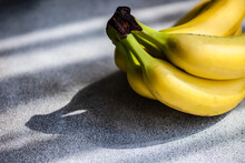 Bunch Of Fresh Bananas On A Table In Sunlight