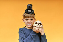 Angry Boy With Vampire Teeth Holds A Skull In His Hands. Halloween Image.