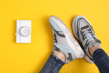 Female Legs In Fashionable Jeans And Sneakers On Yellow Background With Retro Camera/ Travel Concept