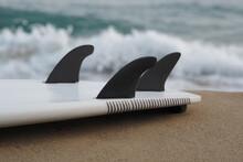 Close-up. Black Surfboard Fins Against Ocean Wave.