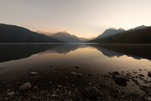 Smooth Pebbles Form The Shore Of Bowman Lake In Glacier National Park Montana. Early Morning Light Makes Silhouettes Of The Distant Mountains.