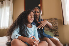 Niña Afroamericana Haciendo Un Gesto De Dolor Mientras Su Mamá Cepilla Su Cabello