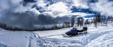 Scenic Panorama View Of Snow Mobile Standing In Deep Snow At Mountain Slope At The Beginning Of Snow Storm, Wild Mountain Birches