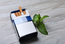 Pack Of Menthol Cigarettes And Mint On Light Wooden Table