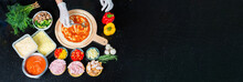 Top View Of Chef Is Spreading Tomato Sauce On Pizza Dough With A Metal Ladle And Pizza Ingredients, Spices For Cooking Pizza's Restaurant Or Homemade. Copy Space For Text. Banner