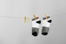 Two Socks Hanging On Rope Against Grey Background
