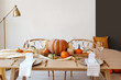 canvas print picture - Dining table with pumpkins near light wall