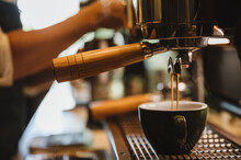 Closeup Of Hands Of A Young Male Barista Pouring Milk Making Latte Art In A Freshly Brewed Coffee In Cafeteria Counter For Customer