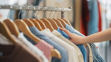 Close Up Shot Of Clothing Rack With Colorful Stylish Items. Shopping Center Interior. Modern Fashionable Shop, Clothes For Every Taste. Fashionable Design, Quality Sustainable Materials. No People.