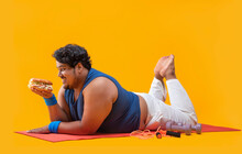 A Fat Man Lying On Yoga Mat Greedily Devouring  A Burger In Hand With Dumbles And Skipping Rope Kept Beside.