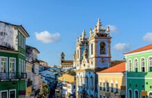 Colorful And Ancient Colonial Houses Facades And Historic Church Towers In Baroque And Colonial Style With Blue Sky In The Famous Pelourinho District Of Salvador, Bahia