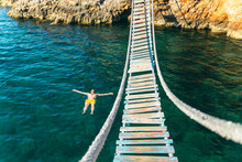 Man Floating In Sea Water On Back. Bay With Rocky Beach And Suspension Bridge