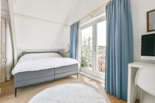 Light Bedroom Interior With Comfy Bed Placed Near Window