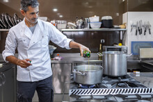 Chef Pouring Oil Into Saucepan With Boiling Water