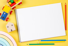 Top View To Blank Open Sketchbook Notebook With Colored Pencils And Educational Wooden Kid Toys And On Yellow Background. Early Education, Kindergarten, Preschool, Learn And Play Concept