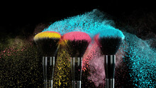 Soft Cosmetics Brush Releasing A Cloud Of Colored Face Powder.