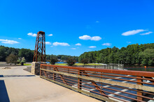 A Rust Colored Bridge Over The Lake Along A Smooth Footpath Surrounded By Lush Green And Autumn Colored Trees With Blue Sky At Lake Peachtree In Peachtree City Georgia