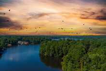 A Breathtaking Aerial Shot Of The Still Blue Waters Of The Lake With Vast Miles Of Lush Green Trees With Homes And Boat Docks And Powerful Clouds At Lake Peachtree In Peachtree City Georgia
