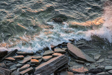 Top View Of A Stormy Ocean With Foamy Waves Rolling And Crashing On The Rocks With A Splash