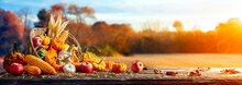 Basket Of Pumpkins, Apples And Corn On Harvest Table With Field Trees And Sky Background - Thanksgiving