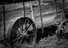 Black And White Image Of An Old Wooden Cart With Rusted Metal Wheels. The Wood Is Weathered And Rotting. The Viewer Gets A Good Impression Of What Life And Transportation Was Like Many Years Ago.