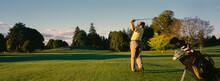 Panorama Of Man Swinging Golf Club On Pristine Golf Course