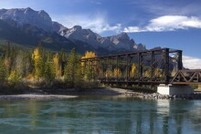 Engine Bridge, An Old Iron Truss Railway Structure, Relic Of Mining Bygone Days Across Bow River In Canmore, Alberta With Canadian Rocky Mountain Peaks Landscape On Horizon