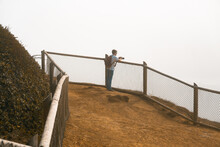 Man With Camera On Cliff Taking  Photograph