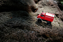 A Red Firefighting Toy Truck Is Placed On The Surface Of Irregular Bumpy Rock Formed By Volcanic Eruption