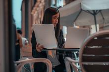 Joven Gestora De Pelo Oscuro Sujetando Unos Papeles Con Informes Y Resultados Mientras Está Sentada En Una Cafeteria Del Pueblo Revisando Su Ordenador Laptop Por La Noche Terminando Su Labor