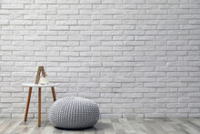 Comfortable Knitted Pouf, Table And Decor Elements Near White Brick Wall Indoors, Space For Text. Interior Design