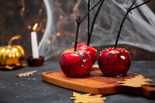 Red Apples In Caramel With A Festive Halloween Decor, An Original Treat For A Festive Halloween Table Decorated With Spiders And Cobwebs, Copy Space For Text