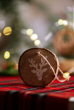 Christmas Ornament Round Wooden With The Drawing Of A Reindeer. Red Checkered Tablecloth